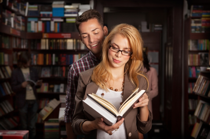 young couple reading a book in a library