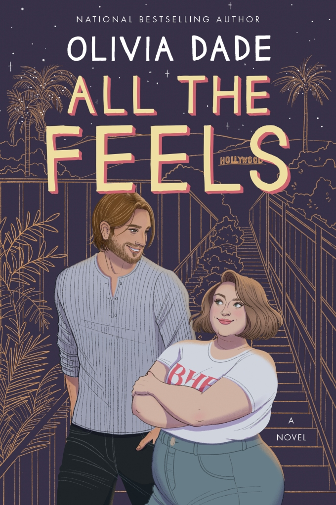 Cover of ALL THE FEELS by Olivia Dade. The illustrated image shows a man and woman on a steep, lengthy set of stairs at night under a starlit sky with palm trees and the Hollywood Sign in the background. The man is handsome, with golden brown hair and a beard, and is smiling down at the much shorter woman, who looks reluctantly amused. She is fat and is wearing a shirt reading BHE (for Big Harpy Energy). Both are white.